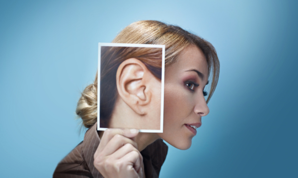 Woman holding enlarged photo of her ear up to her head where her ear should be