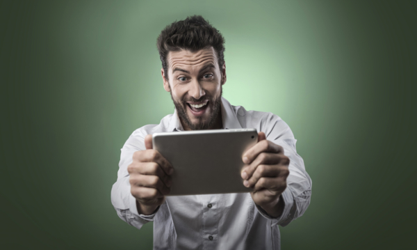 Man watching video on tablet and laughing